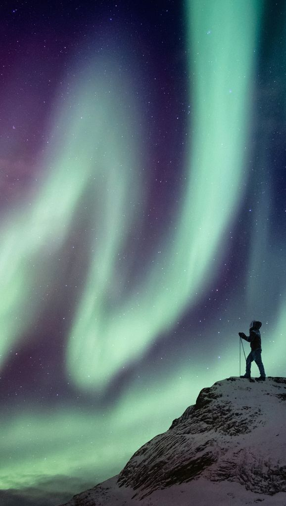 Person on a mountain top looking at aurora borealis