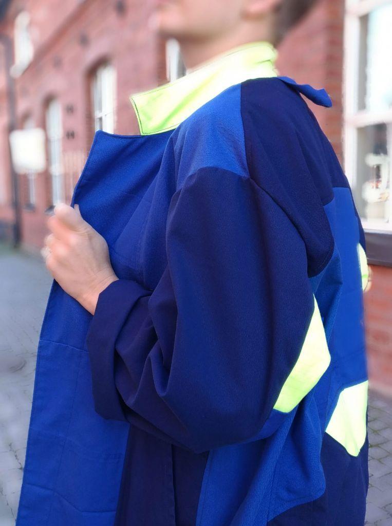 Mallin päällä on sininen takki, joka on koottu erilaisista palasista