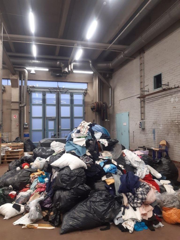 Tekstiilejä ja jätesäkkejä suuressa kasassa