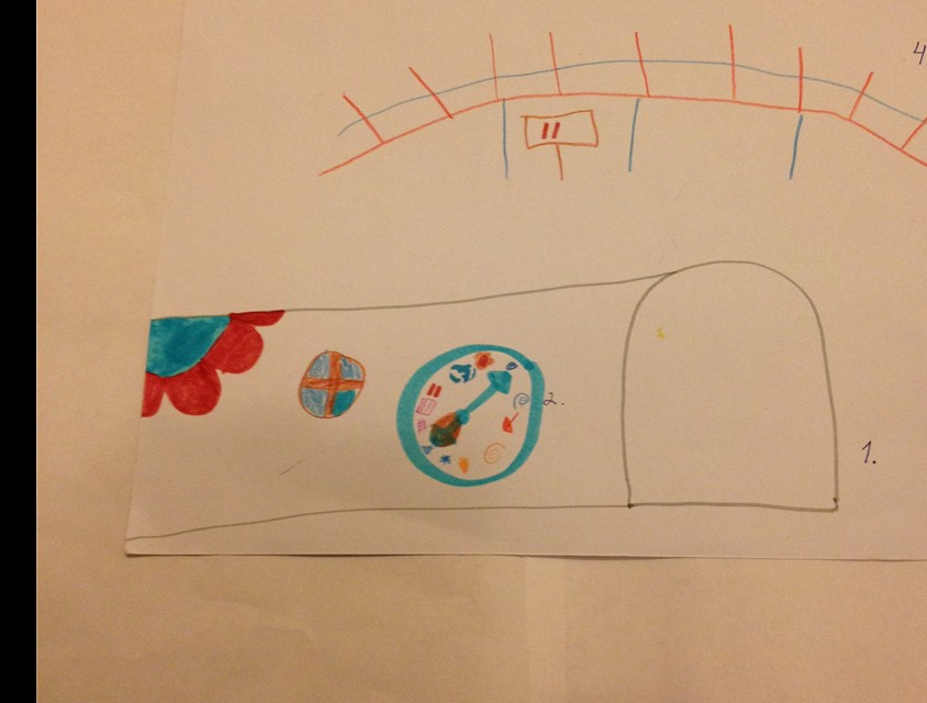 """""""Tunneli, josta voi mennä läpi. Siinä on ikkuna, ettei siellä oo ihan pimeetä. Mut sieltä saa vaan mennä läpi, se on levee, että siellä mahtuu menemään ja peruuttamaan pyörätuolilla ihan hyvin. Ja ramppi tai silta, jota pitkin voi mennä."""" Hankkeen työpajassa tuotettu lapsen piirros esteettömästä tunnelielementistä. Kuva: Kaisa Voutilainen."""