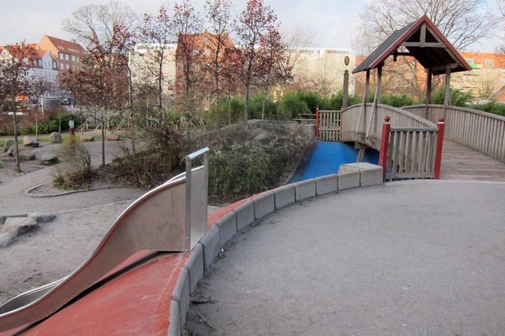 Maastonmukaisen liukumäen yläpäähän pääsee toiselta puolelta portaita pitkin, toiselta puolelta esteettömästi leveää, kovapintaista kulkuväylää pitkin.