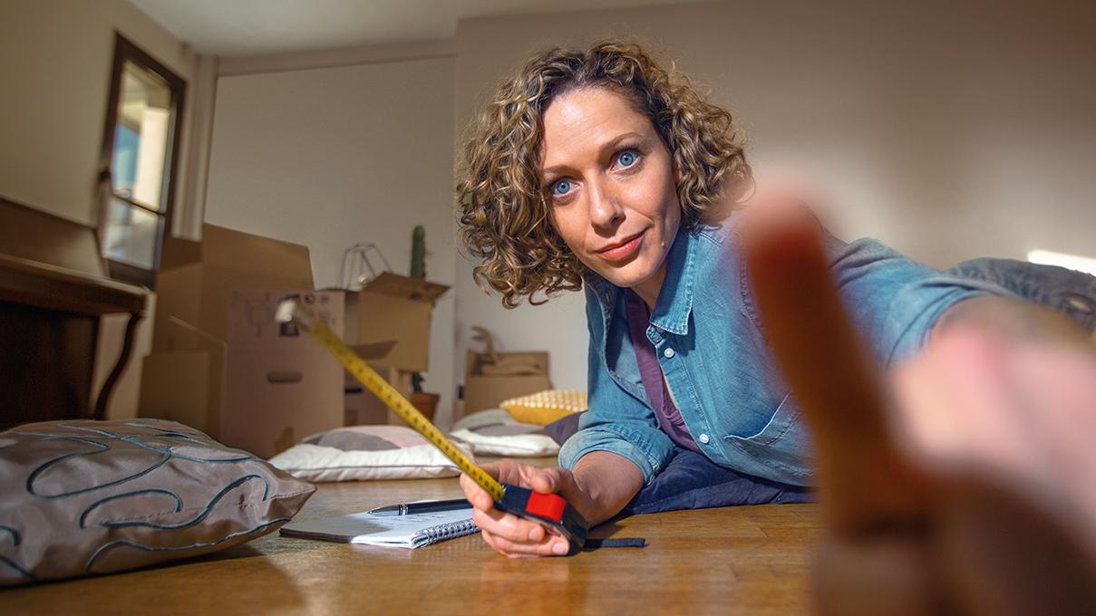 """Femme en plein déménagement tenant un mètre et faisant un signe """"attention"""" de la main."""