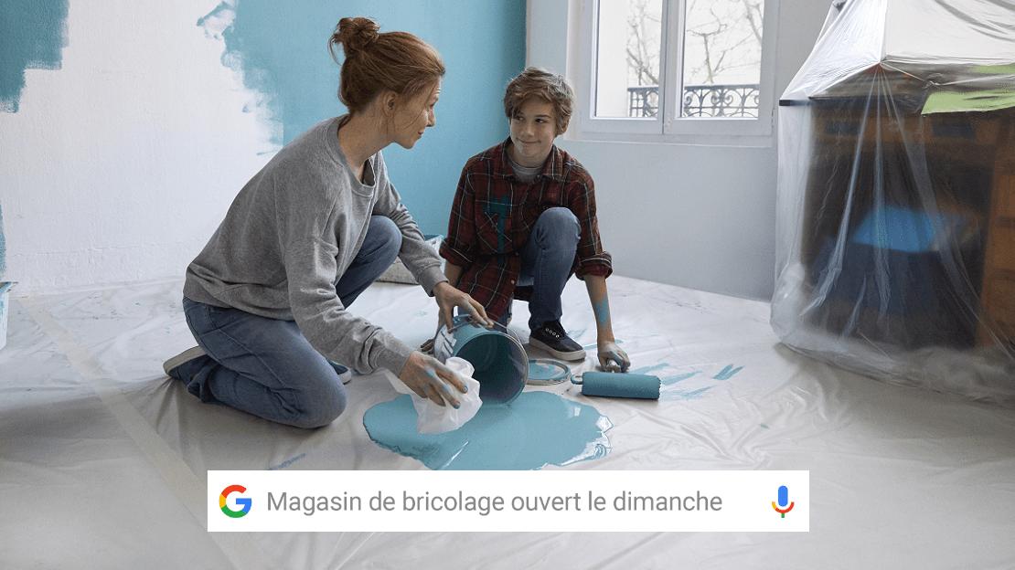 Une mère et son fils repeignent une pièce. Recherche Google d'un magasin de bricolage ouvert le dimanche.