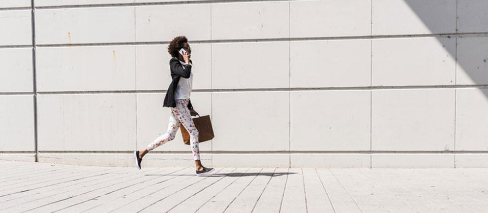 Femme portant un grand sac-à-main, courant en pleine rue, téléphone à l'oreille.