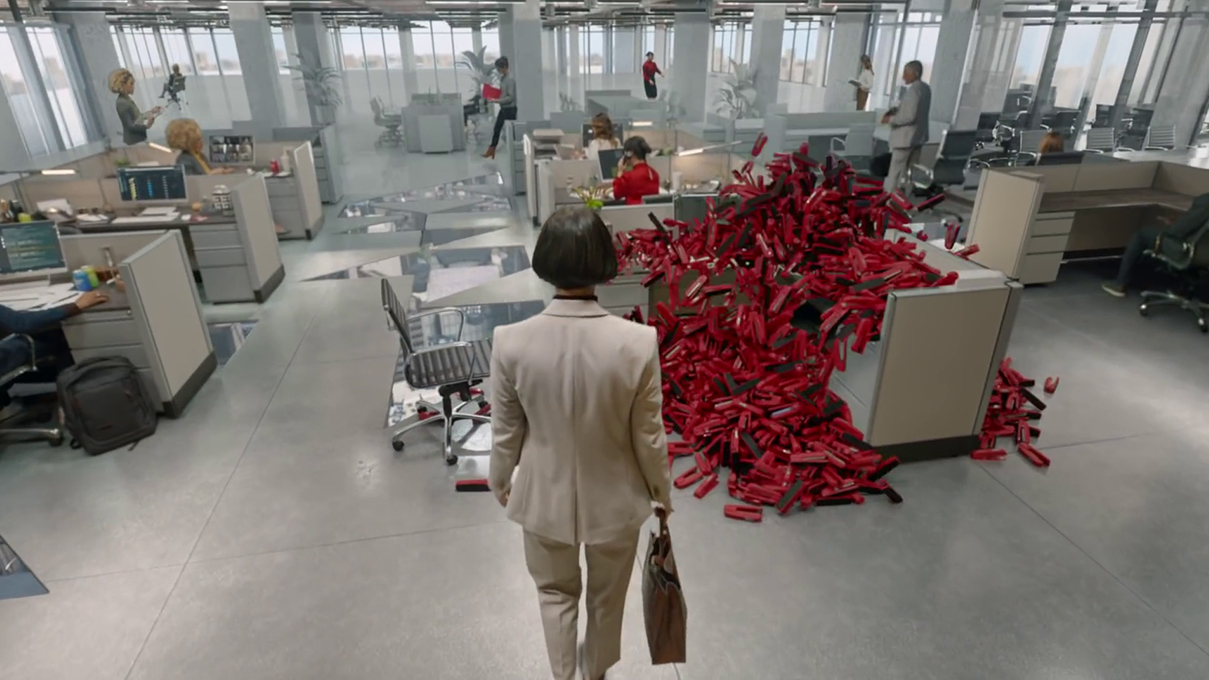 """In Verizon's """"The Reset"""" campaign, a woman with a severe bob haircut, white suit, and attaché walks through an office of cubicles to a desk overflowing with an explosion of red staplers."""