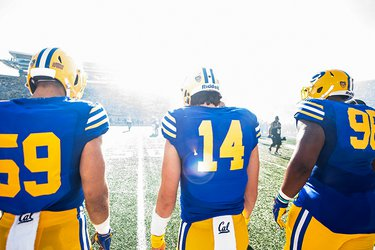 backs of football players in uniform