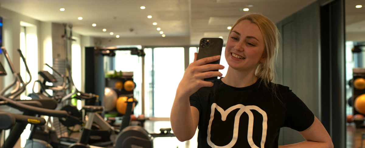A smiling urban therapist is holding up the phone for a video call. She is standing with her back to a mirror in a gym.