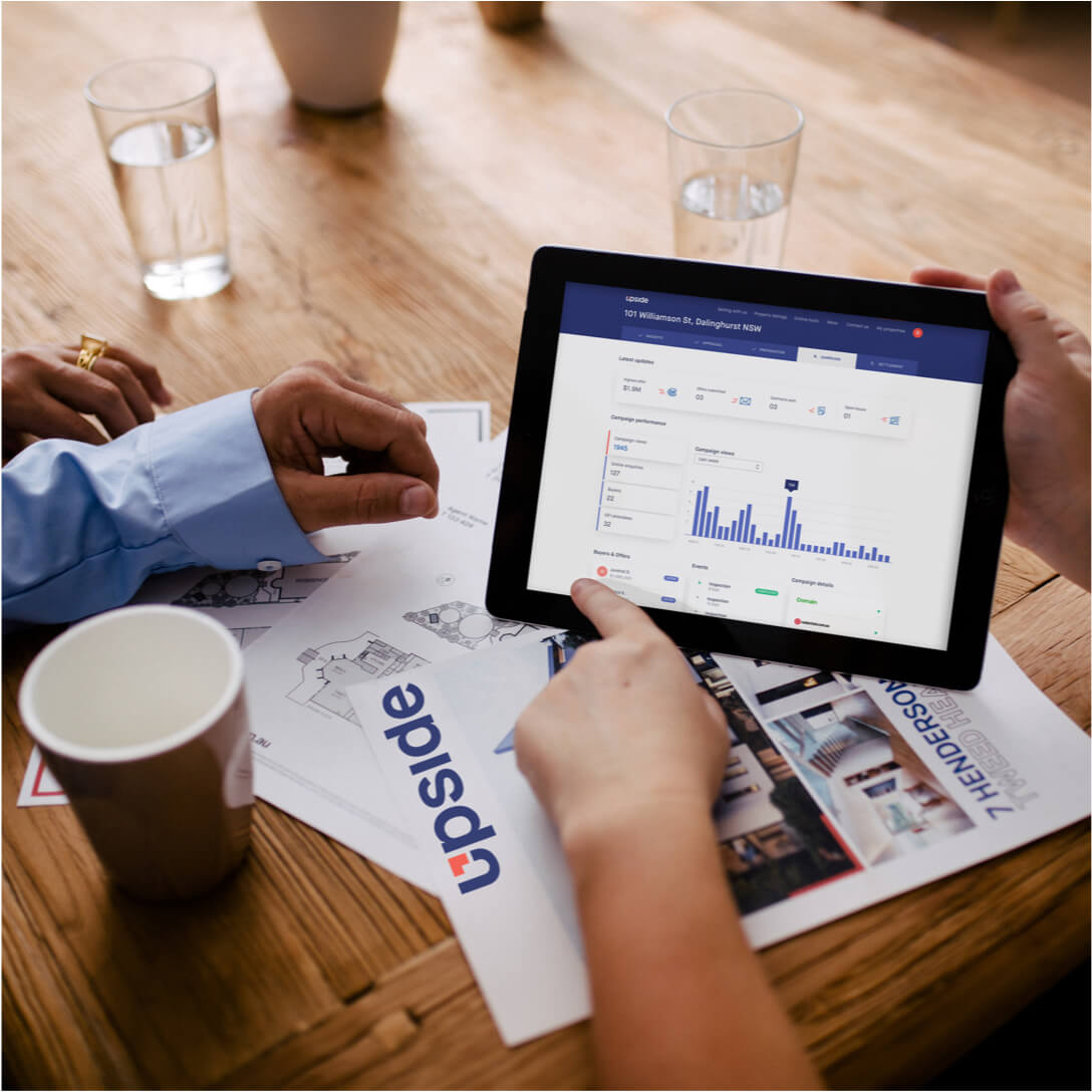Tablet with Upside property dashboard to follow buyer interest with graphs