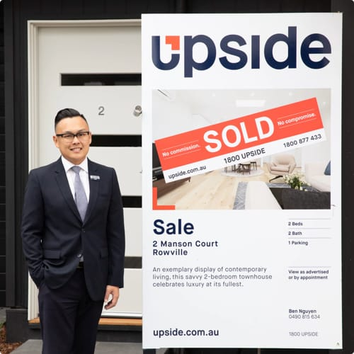 Upside Agent Ben in standing next to a signboard of a sold property