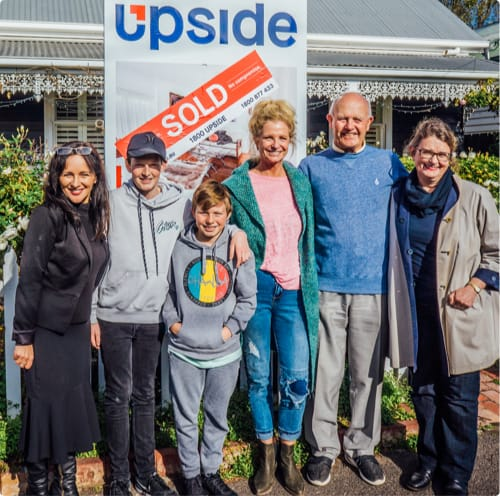 Family standing in front of their sold property