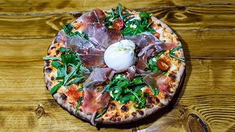 Salcë domate, proshutë krudo, pomodorini, rukola, burrata e freskët. Pizza bëhet me brumë pa maja në furrë druri.