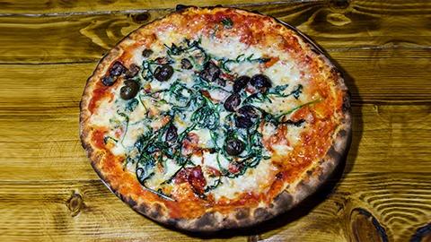 Salcë domate, mocarela fior di latte, esencë hudhre dhe speci djegës, pomodori, sallam pikant, grana, ullinj, rukola të gatuara. Pizza bëhet me brumë pa maja në furrë druri.