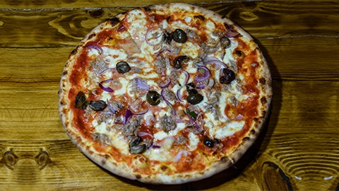 Salcë domate, mocarela fior di late, esencë hudhre, spec, pomodorino, proshutë koto, kërpudha, ullinj. Pizza bëhet me brumë pa maja në furrë druri