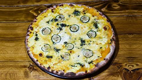 Mocarela fior di latte, krem kungulli, rrota kungulli, gorgonzola pesto, grana dhe salcë domate sipas dëshirës. Pizza bëhet me brumë pa maja në furrë druri