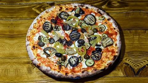 Pizza vegjetariane me salcë domate, mocarela fior di late, patëllxhan, kunguj, spec i kuq, kërpudha, thajm, borzilok, ullinj, vaj ulliri. Pizza bëhet me brumë pa maja në furrë druri