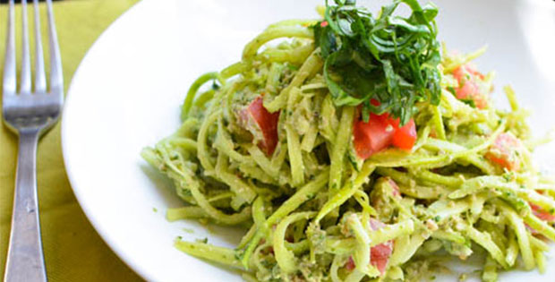 raw zucchini noodles with pesto in a bowl