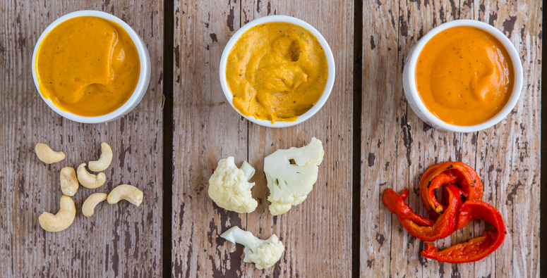 Three bowls of vegan nacho cheese sauce with cashews, cauliflower, and roasted red peppers in front of them.