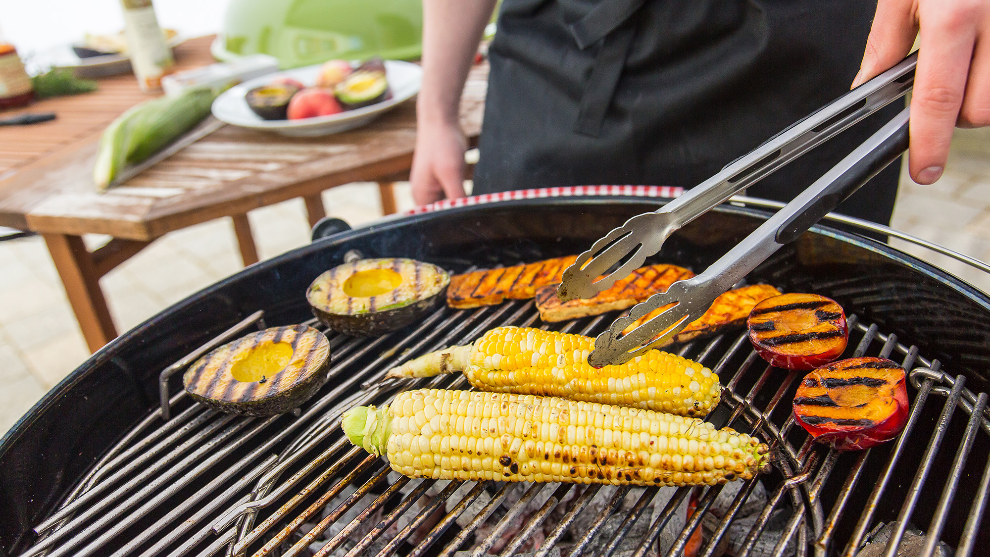 someone grilling corn, tofu, peaches, and avocados for a vegan BBQ