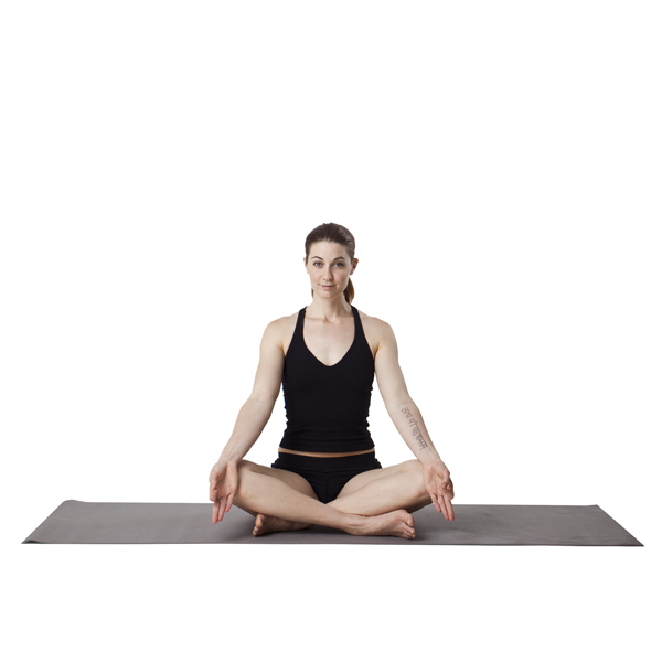 woman doing a sukhasana yoga pose (sitting cross legged)