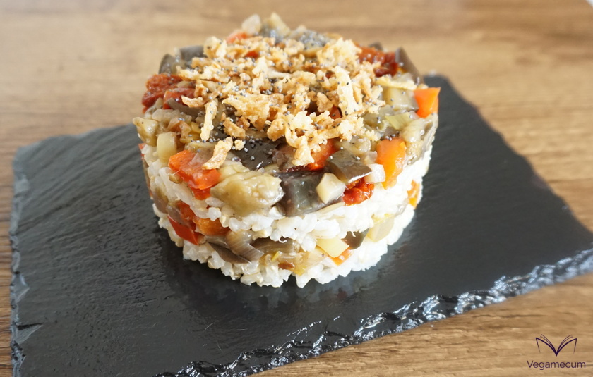 Timbale of brown rice and vegetables with crispy onion topping and poppy seeds