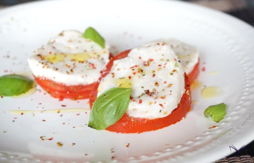 Fresh vegan mozzarella on tomato slices with basil, oil and spices