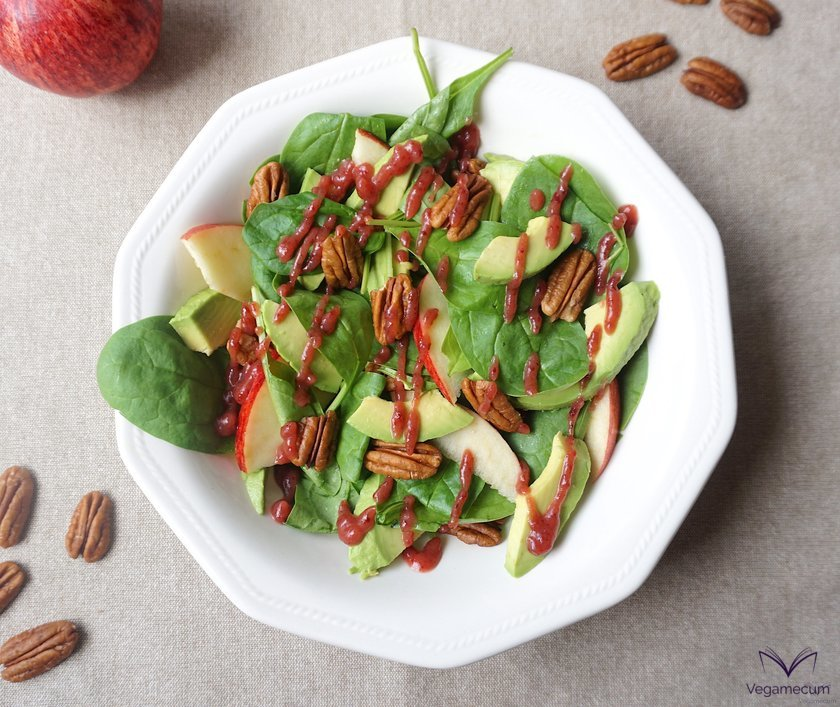 Aerial shot of baby spinach, avocado, walnut, and apple salad with finished cranberry vinaigrette