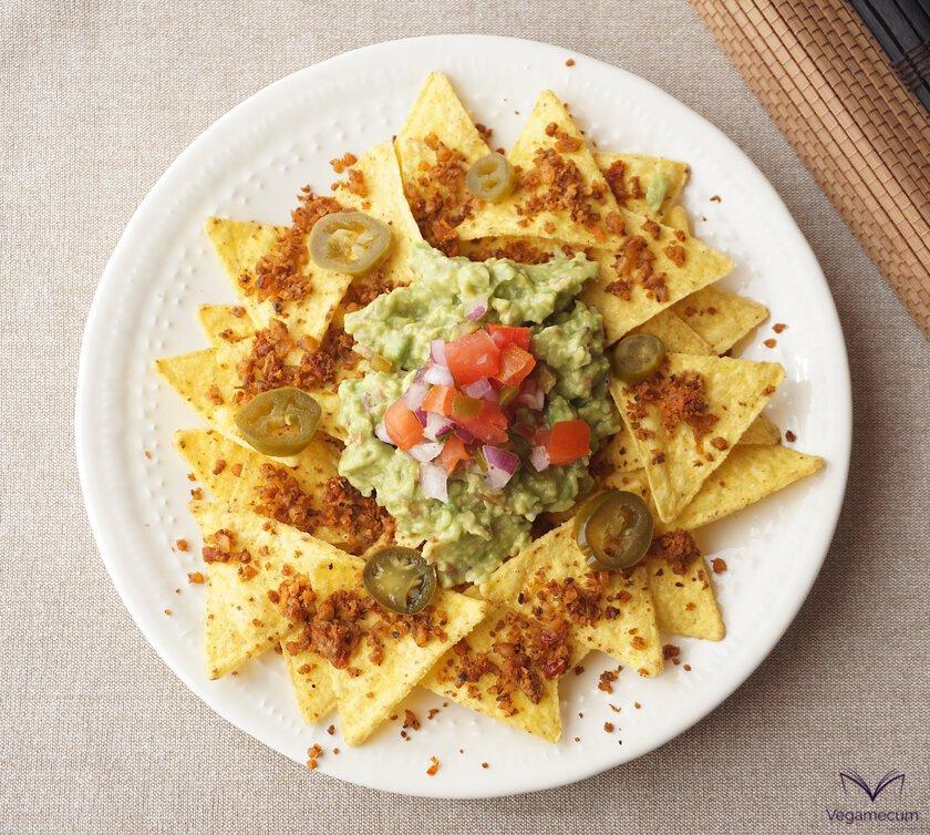 Plano cenital de 'Carne de nuez sabor chorizo' sobre nachos con guacamole y pico de gallo