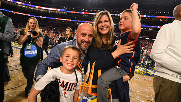 Erich Bacher with his wife Carley and sons E.J. and Christian on the court at U.S. Bank Stadium in Minneapolis, after the University of Virginia men's basketball team won 85-77 over Texas Tech in overtime in the National Championship Game Monday, April 8. NCAA Photo