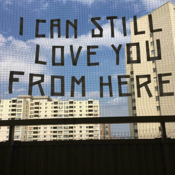 """Image description: A photograph of an outdoor fence with entitled text """"I can still love you from here"""" with a background view of two concrete housing complex skyscrapers."""