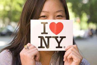 Estudiante extranjero de los programas de inglés de NYU sosteniendo un cartel de I love NY