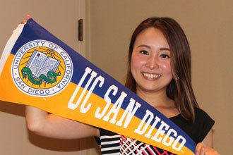 student from the UCSD English language program holding UC San Diego pennant