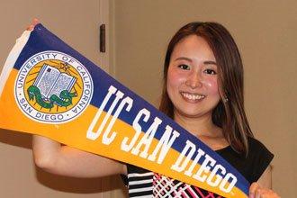 estudiante internacional cursos de inglés de UCSD mostrando el banderin de UC San Diego