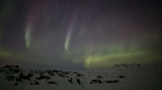 Flashing aurora borealis and deep stars over snow covered lava field, Iceland winter