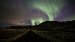 Realistic aurora borealis over country road grassy mountains Iceland 4k