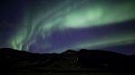 Realistic aurora borealis over countryside grassy mountains Iceland 4k