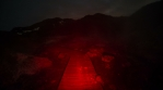 Pathway over mountainous smoky geothermal zone red light dark abstract