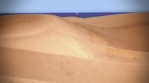 Wind blowing over sand dunes sailboat on horizon Canary Islands Spain artistic