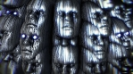 Abstract metallic live form with faces. Sci-fi seamless background