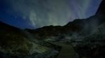 Flashing aurora borealis over geothermal volcanic landscape Krysuvik Iceland