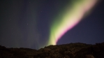Strong bright realistic aurora borealis over rocky volcanic terrain Iceland 4k