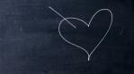 Arrow struck heart. Handwritten chalk on a black chalkboard. Cupid arrow shoots heart