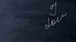 I love you. Handwritten chalk on a black chalkboard. Arrow shot heart shape. Love at school concept.