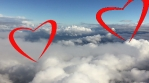 Couple of loving red hearts flying at cloud blue sky together. Red hearts as love and togetherness concept.