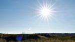 Starburst sun lens flare slow motion pan over grassy field Iceland summer