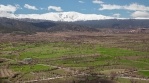 Farmland under snowy Sierra Nevada mountains and passing clouds, Andalucia Spain time lapse