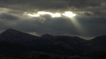 God Beams light rays piercing through dark clouds over Spanish countryside, time lapse