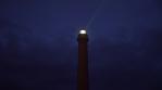 Stone lighthouse casting light beams against a blue twilight sky