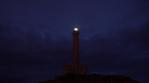 tone lighthouse on hill casting light beams against a blue twilight sky