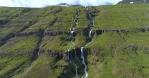 Beautiful remote twin mountain waterfalls, Mjoifjordur Iceland aerial summer day revealing shot
