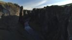 Fjadragljufur glacial canyon river, Iceland sunny morning, drone aerial rising shot
